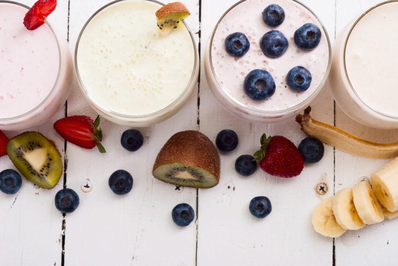 fruit smoothies met eiwit, blauwe bessen, kiwi, banaan en aardbeien op witte houten ondergrond over waarom je meer eiwitten zou moeten eten