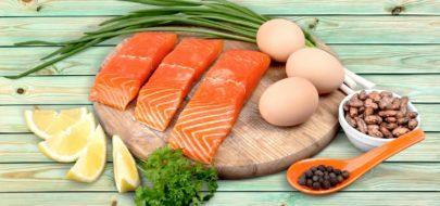 Eiwit uit zalm, eieren, bonen, citroen, peterselie en lenteui op houten plank
