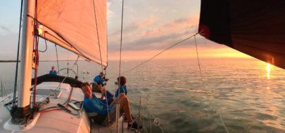 Uit je comfortzone met zeilboot met ondergaande zon
