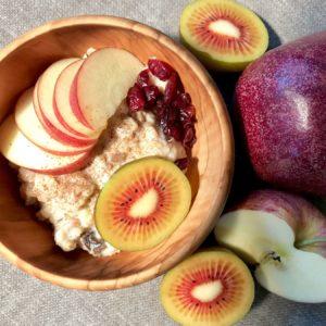 Houten kom met havermout, kaneel, stukjes appel, rode kiwi en granaatappel.