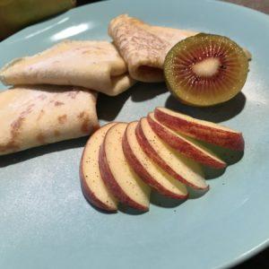 Flensjes met stukjes appel, rode kiwi op en lichtblauw bord
