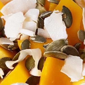 Kwarkontbijt met pompoen, mango, zonnebloempitten in glas