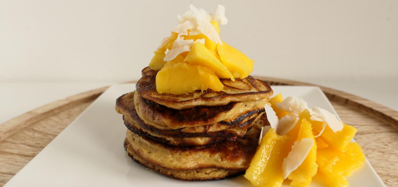 Stapeltje protein pancakes met stukken mango en kokos op bord
