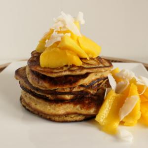 Protein pancakes met stukken mango en kokossnippers op wit bord met houten ondergrond