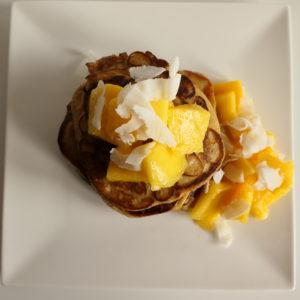 Protein pancakes met stukken mango en kokossnippers op wit bord