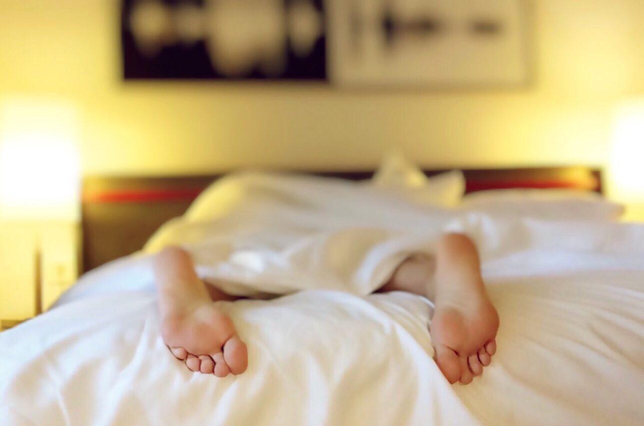 slapen met warm weer in bed met blote voeten en witte lakens