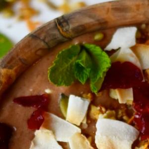 Houten kom met chocolade nicecream. Gedecoreerd met kokosvlokken, munt en cranberry's.